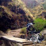 Biker crossing bridge in cusco peru on bike tour peru