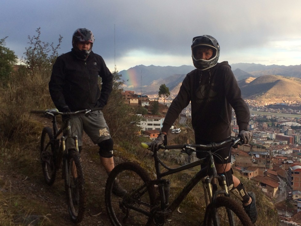 Cusco Biking tour half day bike ride with two bikers overlooking city with rainbow