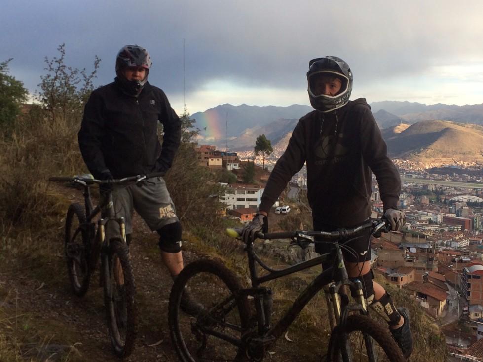 Cusco Biking tour half day bike ride with two bikers overlooking city with rainbow