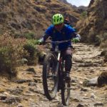 Mountain biker doing a wheelie on a peru bike tour in cusco peru